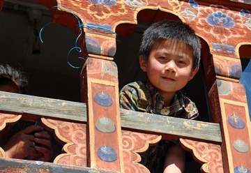 Bhutanese boy looking out a window